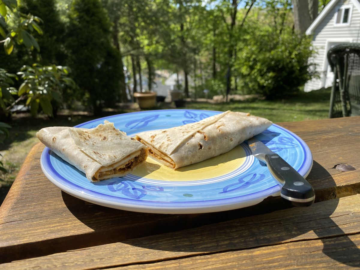 The Bomb burrito, stuffed with beef, cheese, and beans, sits on a decorative blue and yellow plate on a picnic table