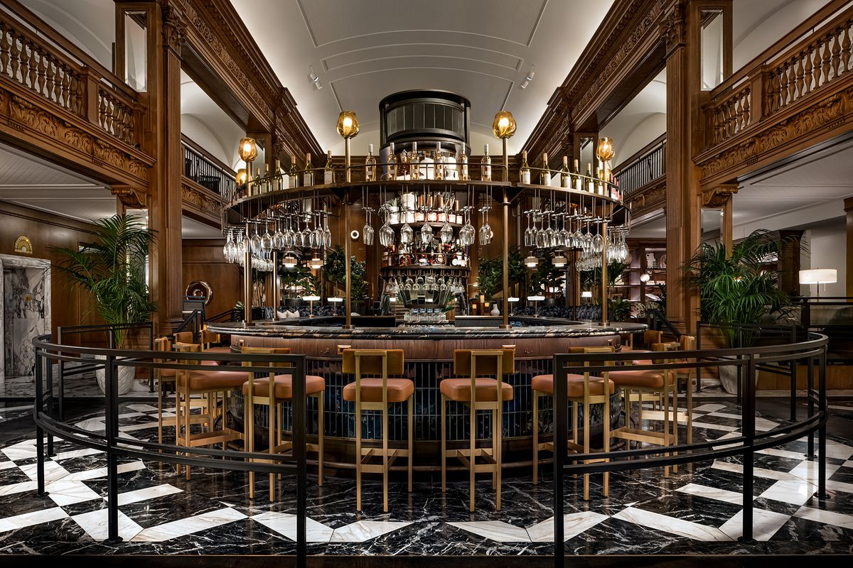 An ornate wood-accented round bar in the middle of Seattle's historic Fairmont Olympic Hotel
