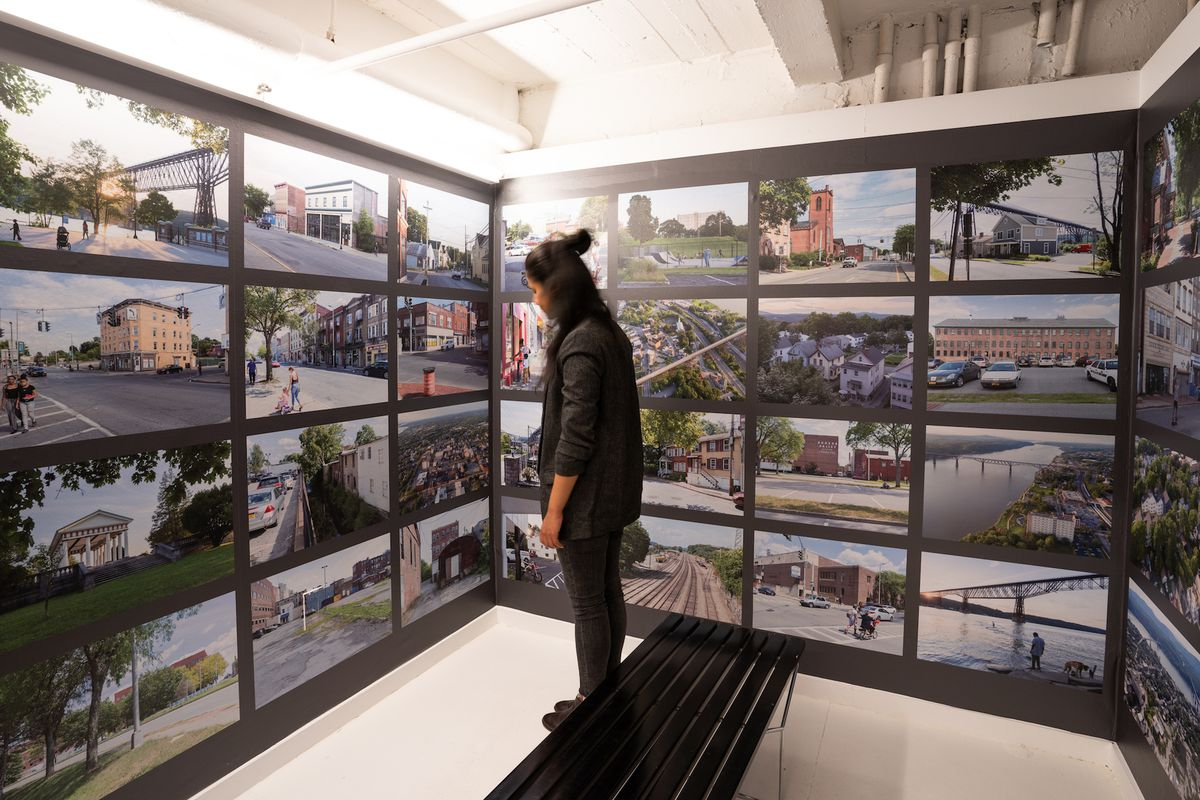 A person standing in front of a wall of photographs of street scenes at a gallery exhibition.