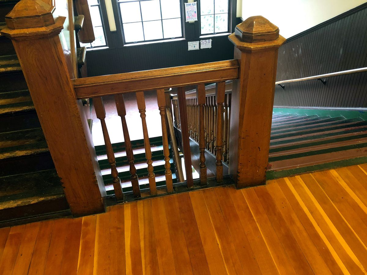 An open stairwell with ornate, exposed oak bannister and railing. it's viewed from a stop with hardwood floors beneath. A landing visible below has large windows and dark brown walls, and the staircase is lined in dark brown wainscoting.
