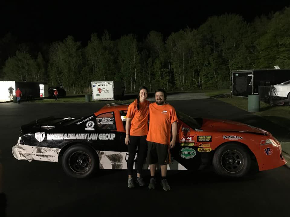 Amanda Conger stands with Cameron Ouellette, both wearing bright orange shirts, in front of his race car at Thunder Road.