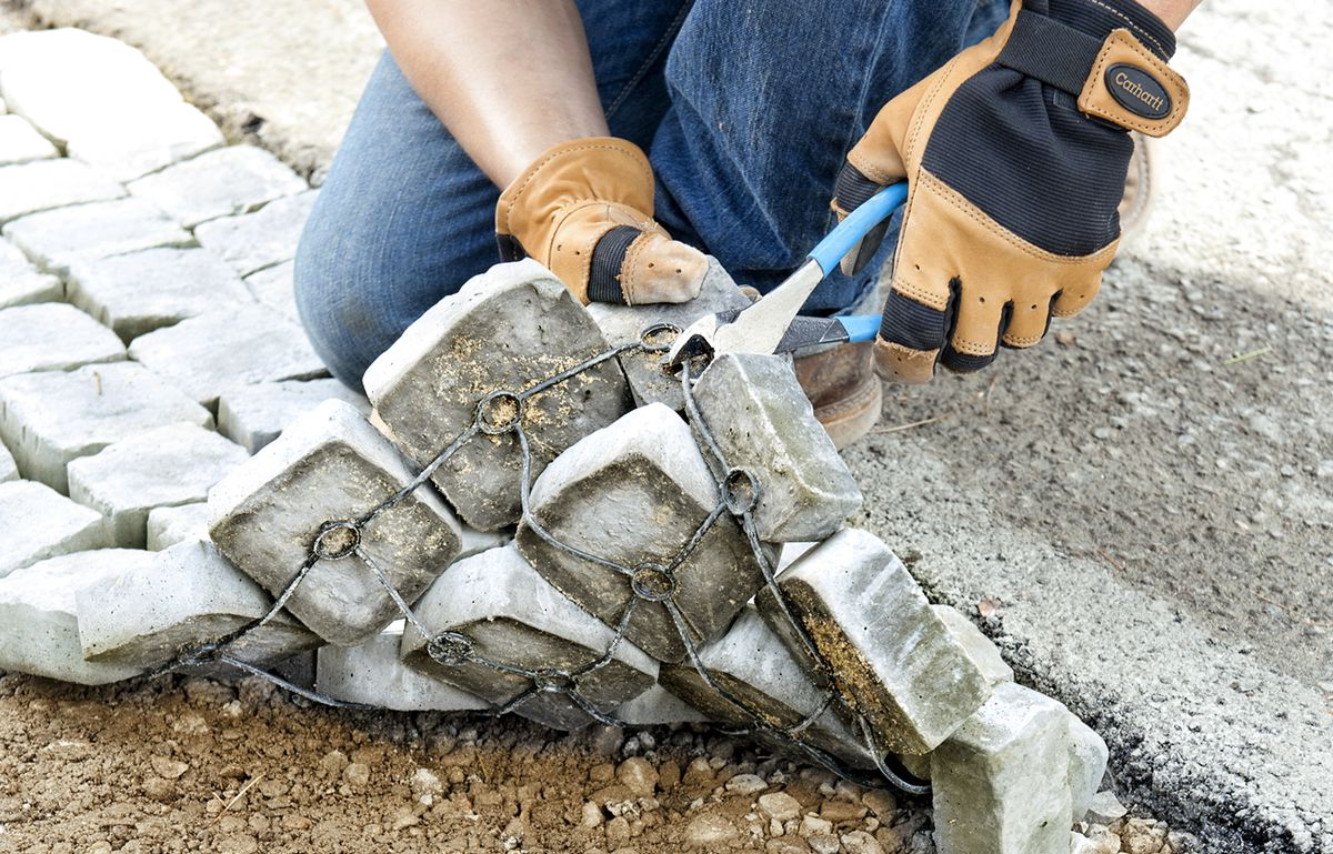 Man Removes Half Cobbles From Grid to Interlace Mats For Driveway Apron