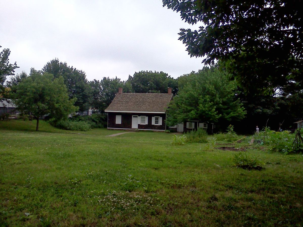 A large brown house in the middle of an expansive green lawn surrounded by trees.