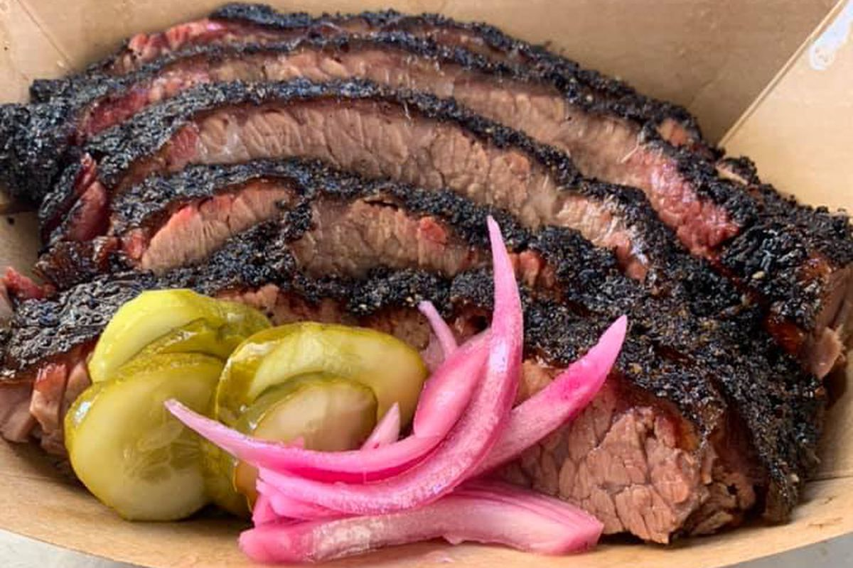 A paper tray of sliced brisket, pickle slices, and onions from Whitfield's