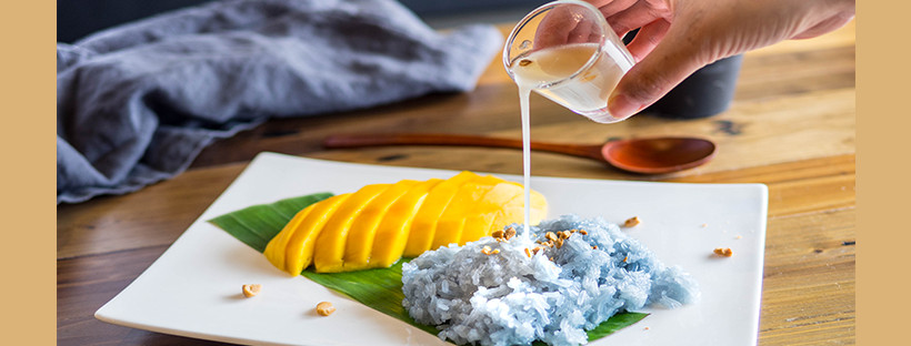 A hand pours sauce over blue sticky rice alongside slices of mango, a dessert dish at Coconut Newton