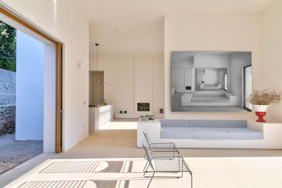 Rectangular white sofa in sunlit living room.