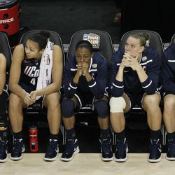 Connecticut players watch action at the end of overtime in the NCAA women's Final Four semifinal college basketball game against Notre Dame, in Denver, Sunday, April 1, 2012. Notre Dame won 83-75.