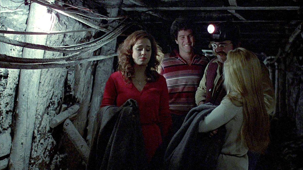 Four people walk down a mine shaft