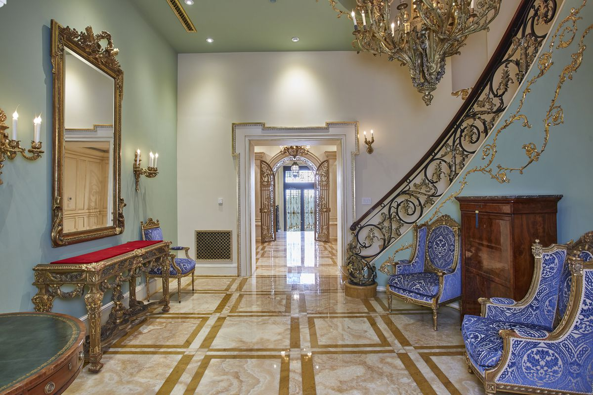 A foyer with marble floors, a staircase with elegant railings, and two blue chairs.