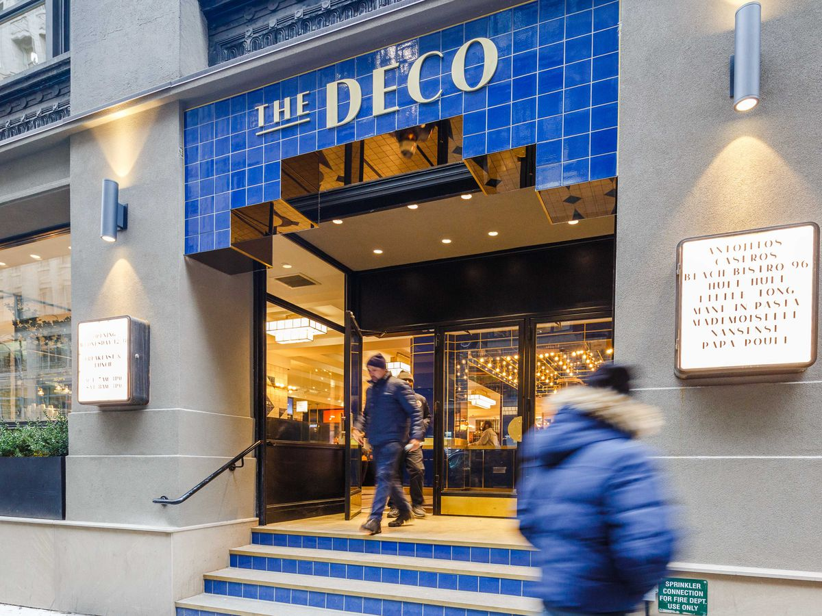 The blue-tiled storefront of the Deco with a sign up top