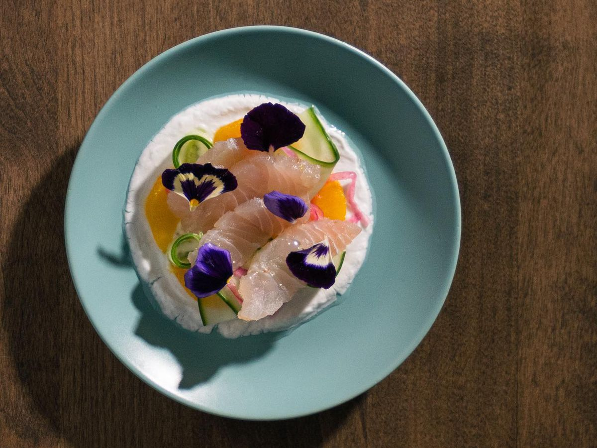 raw fish on top of cream in blue bowl on wood table