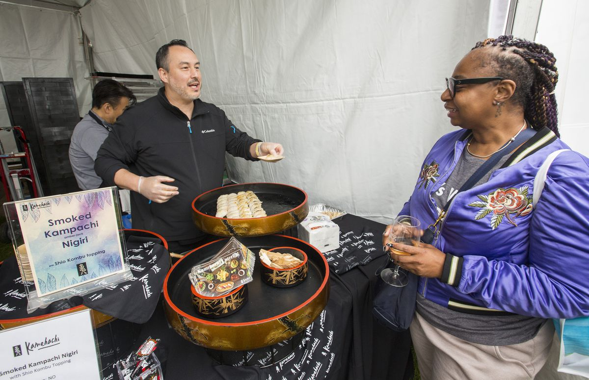 A man stands behind a table offering a festival attendee smoked amberjack nigiri.
