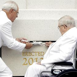 Elder Boyd K. Packer, right, takes his turn putting mortar around the cornerstone of the Brigham City Temple as Elder William R. Walker assists during Sunday's dedication.