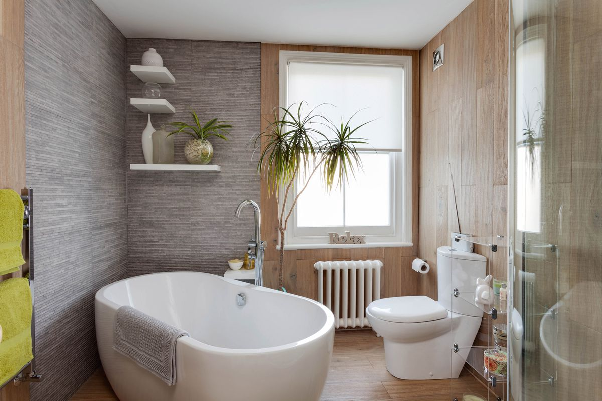 A bathroom with free standing tub and wood laminate floors.