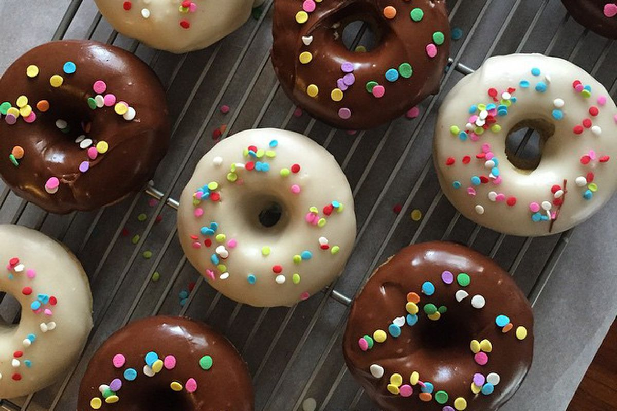 A tray of doughnuts frosted with white and chocolate, decorated with multi-colored sprinkles