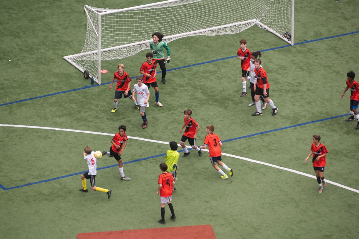 Kids playing a soccer match, seen from above.