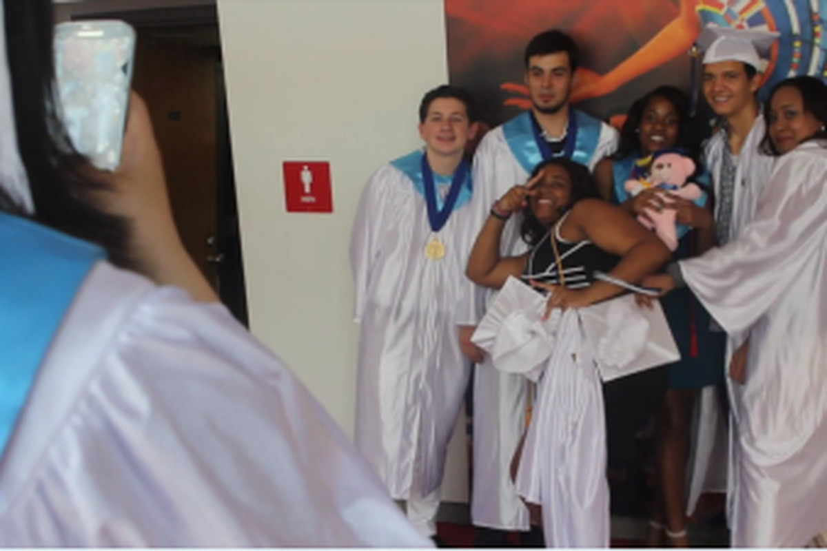 Students take photos before graduating from the closing Christopher Columbus High School.