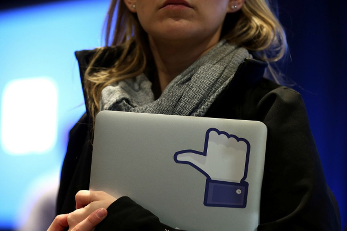 A woman holding a laptop with a picture of the Facebook thumbs up icon in it.