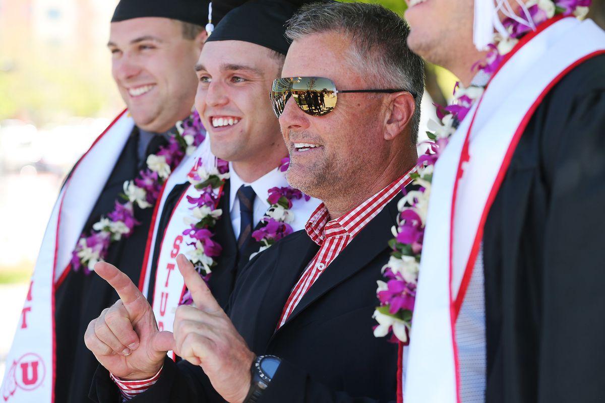 Coach Kyle Whittingham flashes a U with University of Utah football team members during University of Utah graduation in Salt Lake City on Friday, May 5, 2017.