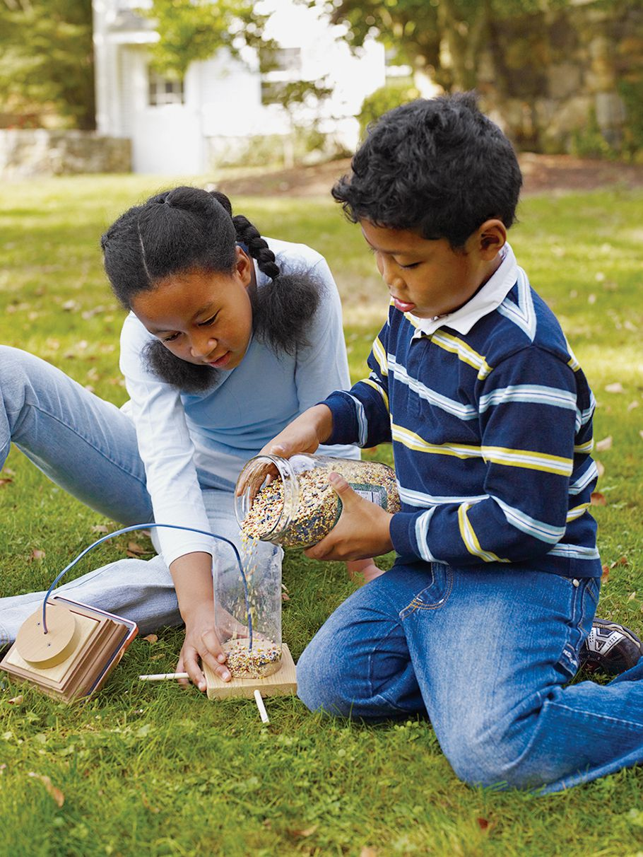 Two children filling a bird feeder with seeds.