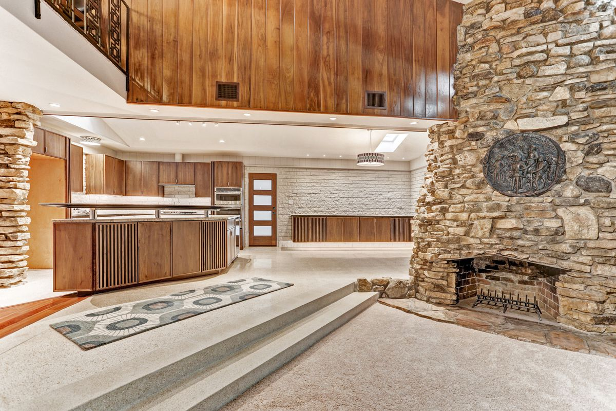 A kitchen with wood cabinets sits next to a stone fireplace.