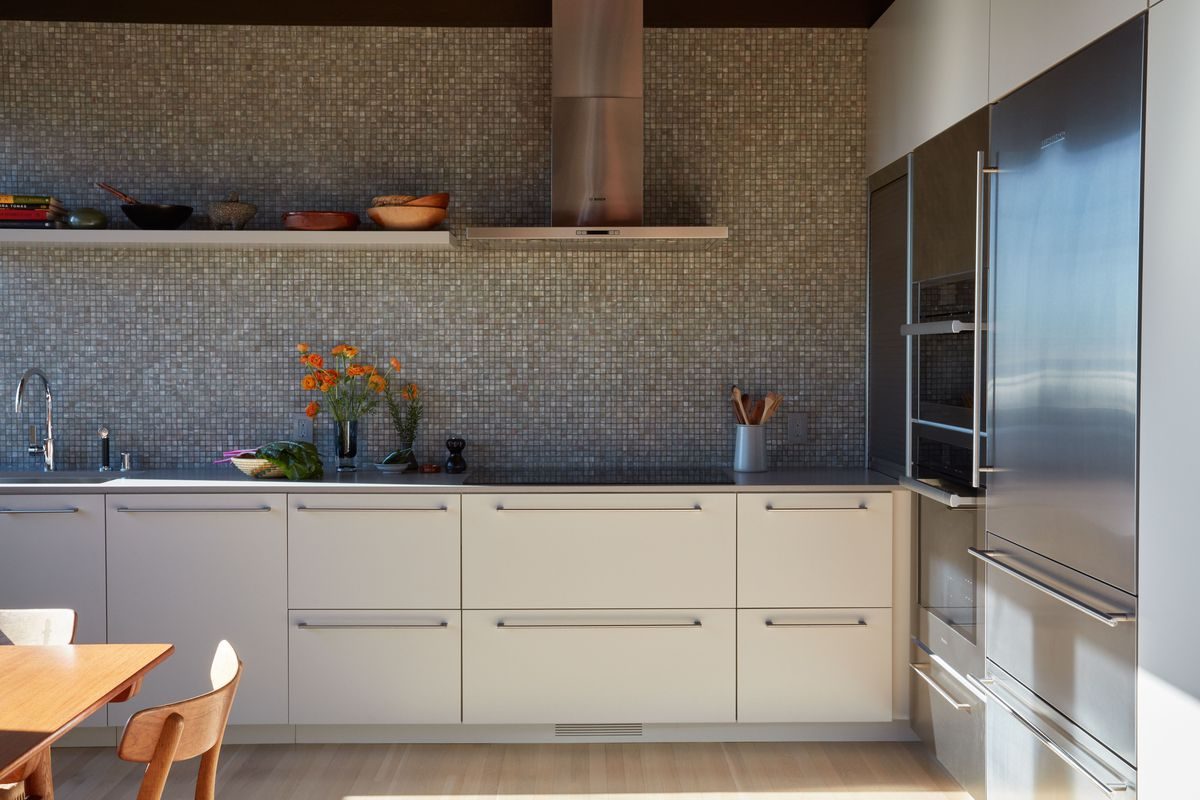 A kitchen. The wall backsplash is grey and white. The cabinetry is off white. There are silver kitchen appliances.