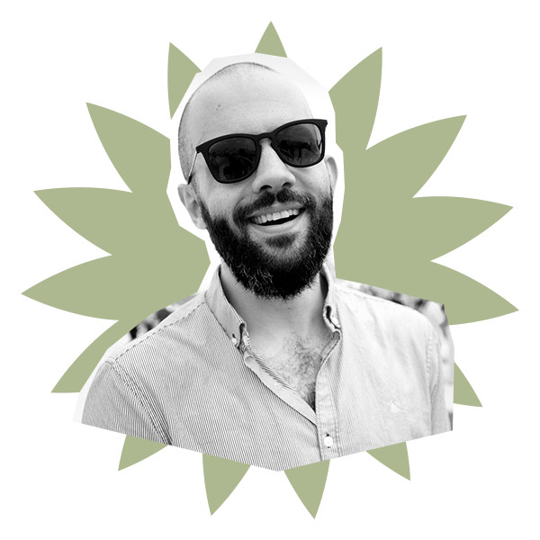In black and white, a bearded and head-shaven Andrew Rea wears sunglasses and a striped button-down.