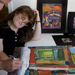 Woods Cross High art teacher Lester Lee and student Brandi Bixler sign their paintings at the Bountiful Davis Art Center.