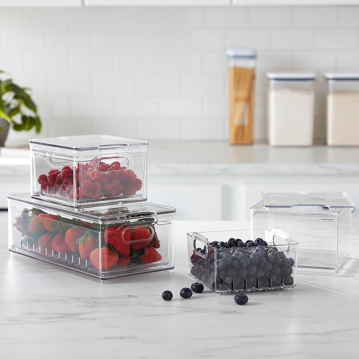 Three clear storage bins containing blueberries, raspberries, and strawberries