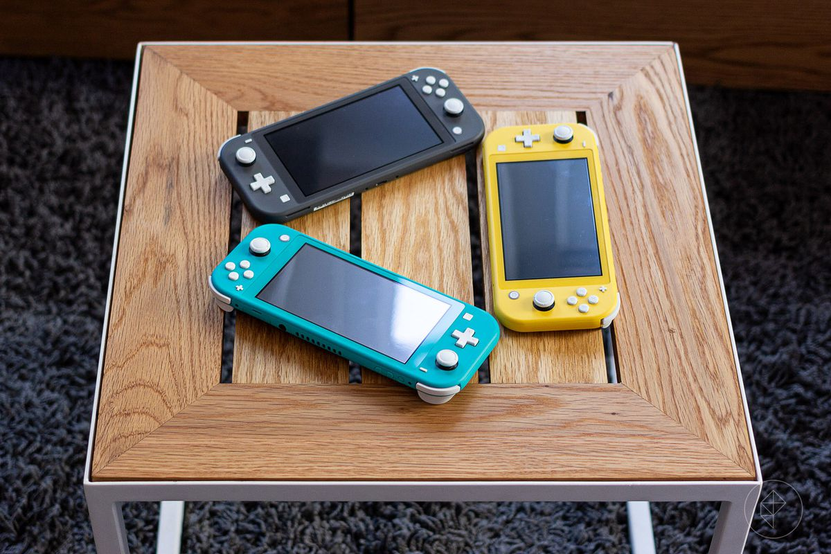 three Nintendo Switch Lite models (gray, yellow, turquoise) sitting on a wooden table