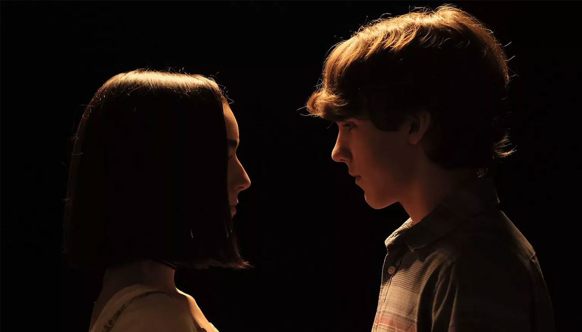 Two young characters face each other in a dark room in Hero Mode