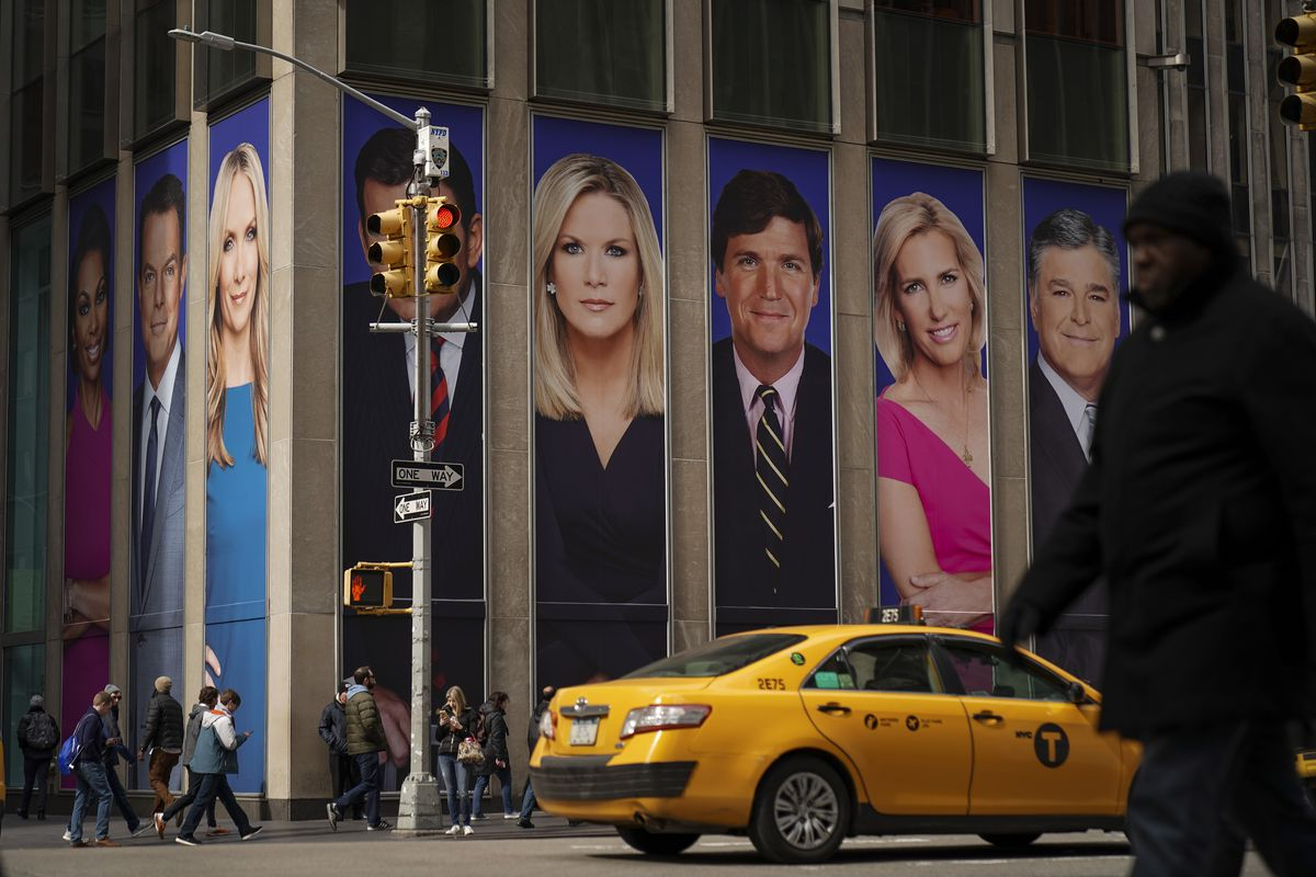 A cab passing by the News Corporation building, which bears advertisements of Fox News personalities (from left) Martha MacCallum, Tucker Carlson, Laura Ingraham, and Sean Hannity, on March 13, 2019 in New York City.
