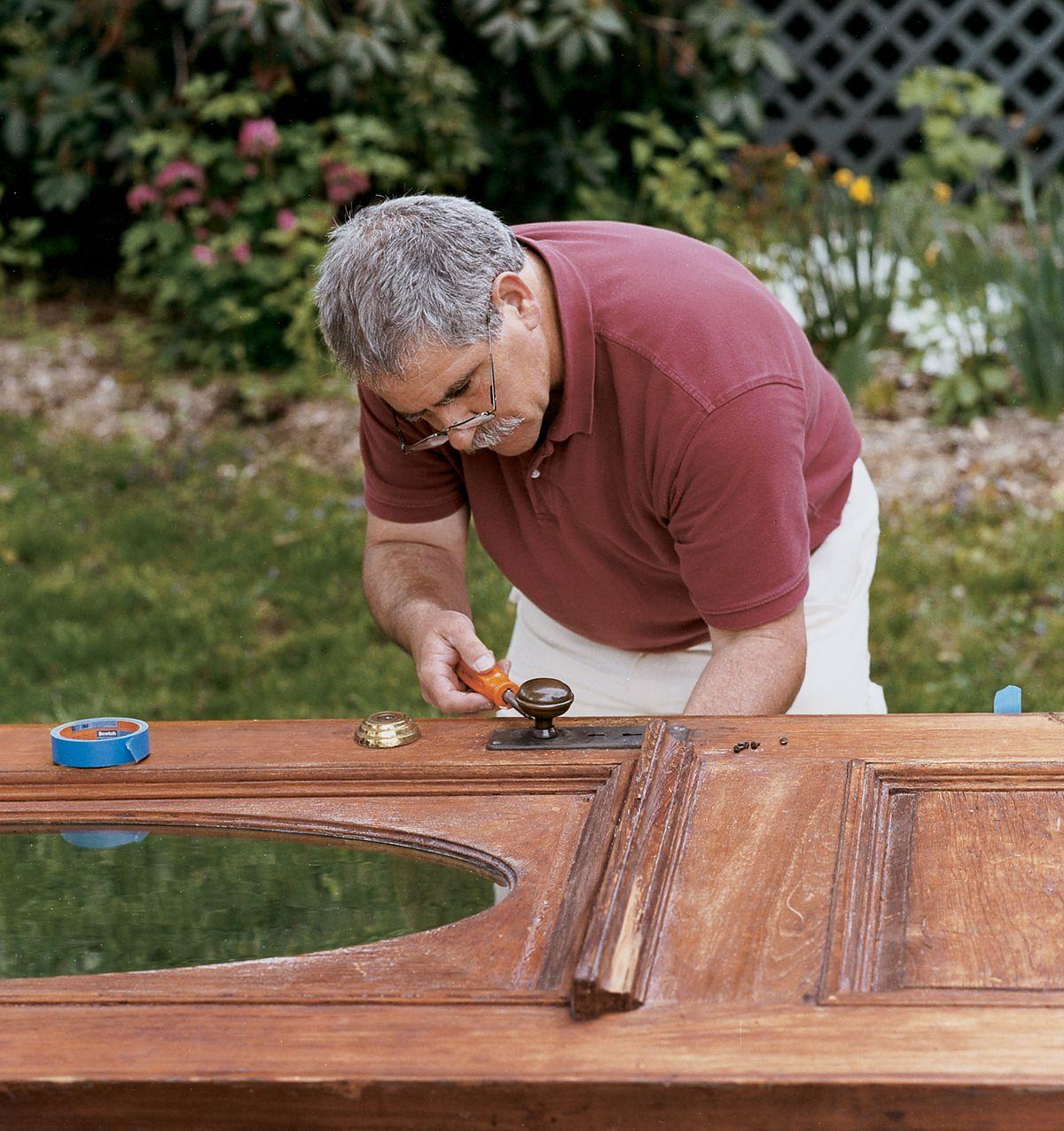 Man Removes Door Hardware To Refinish Wood Door