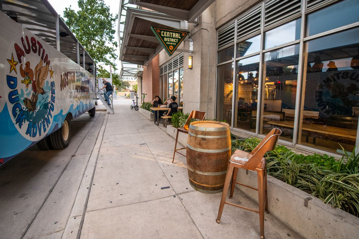 A barrel keg with two bar seats are placed outside of a building and its greenery area on a sidewalk next to a Duck Tour bus
