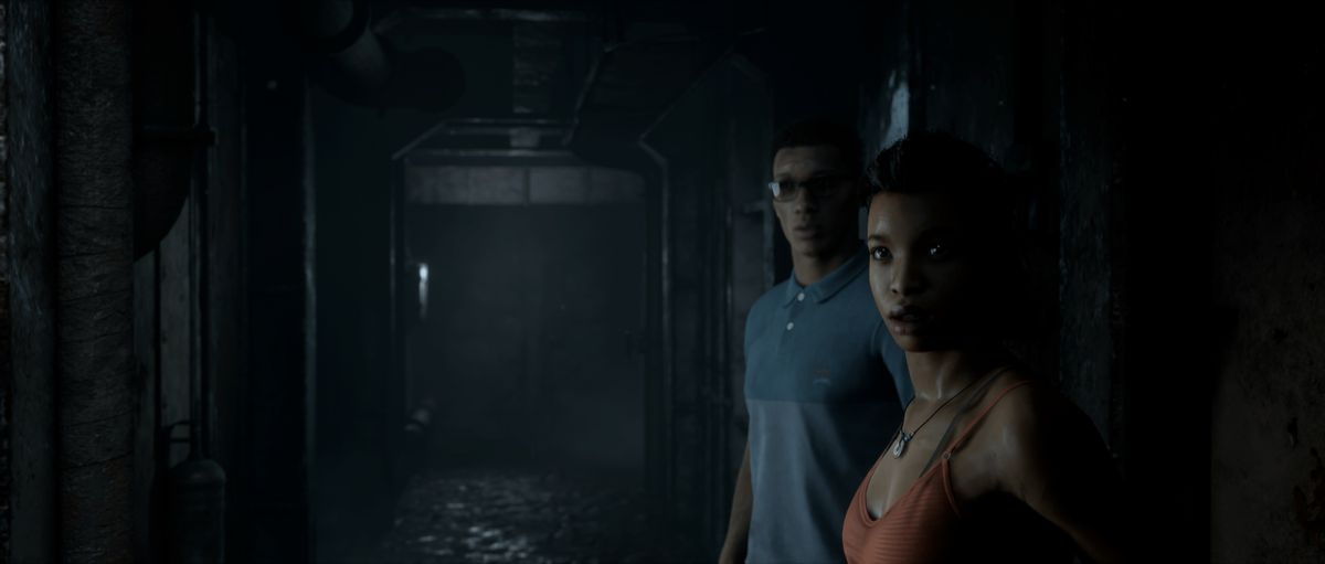 Brad and Fliss, two campaign characters, stand in the dark and gloomy hallway of an abandoned ship in Man of Medan