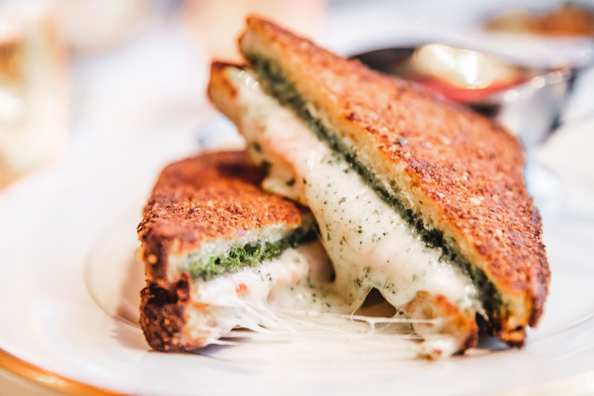 A toasted mozzarella and pesto sandwich cut into triangles stacked on top of each other, connected by strings of cheese.