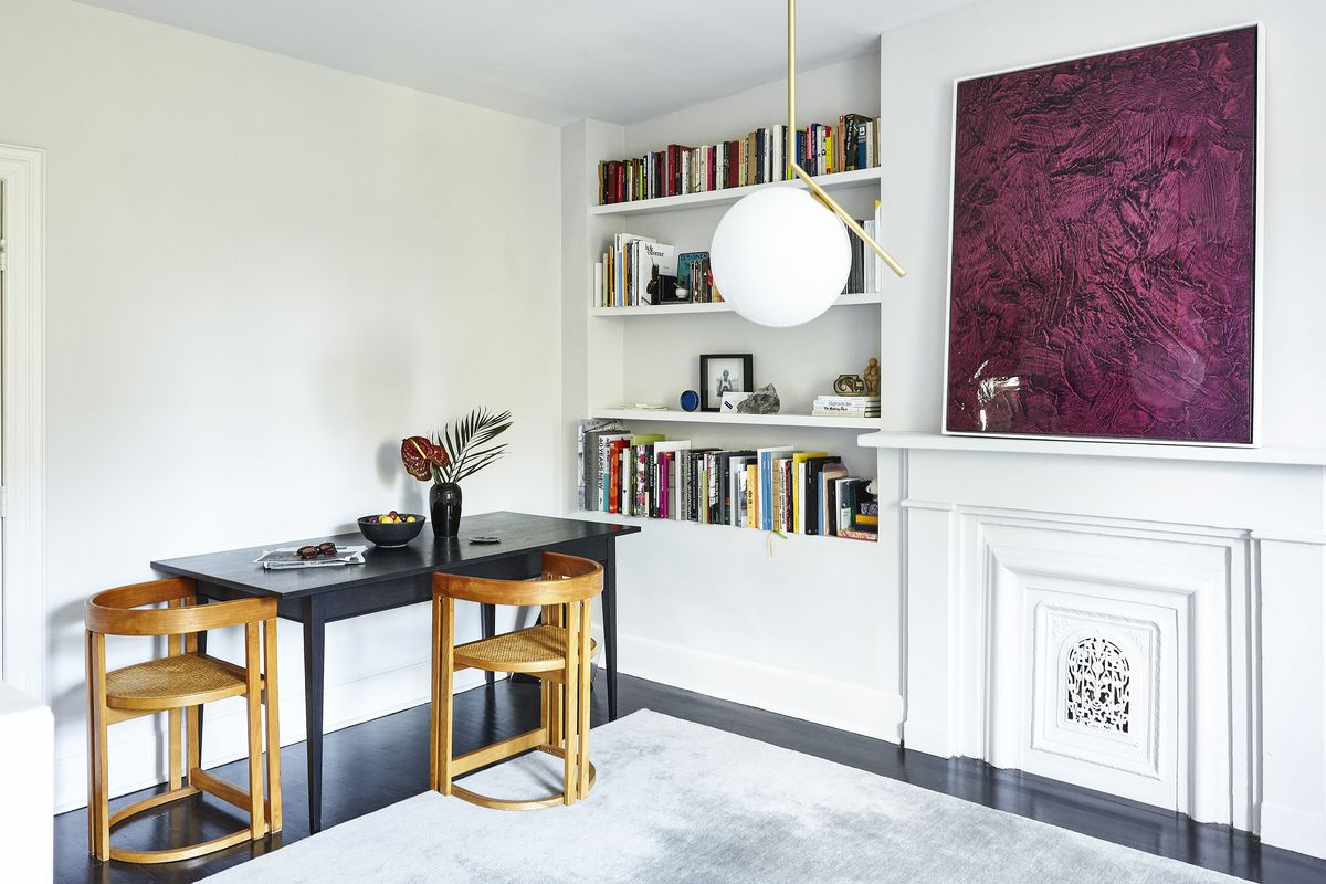 A dining room area. The walls are painted white and there are bookshelves built into the wall which contain an assortment of books. There is a large purple work of art hanging over a fireplace. A black table sits against the wall with two wooden chairs.