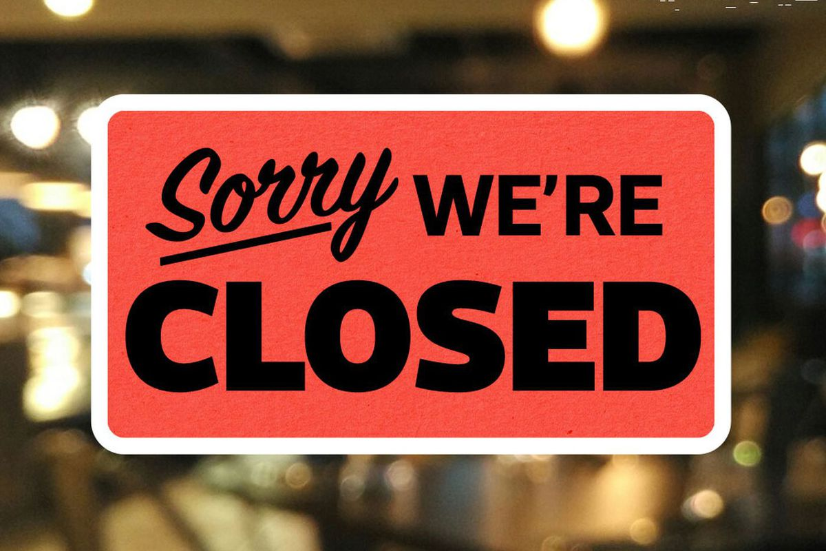 """A """"Sorry, We're Closed,"""" sign in a nondescript window"""