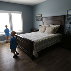 Trayden and Kaiden Vendela walk through one of the boys' bedrooms of their new home in Huntsville, Weber County, on Friday, July 3, 2020.