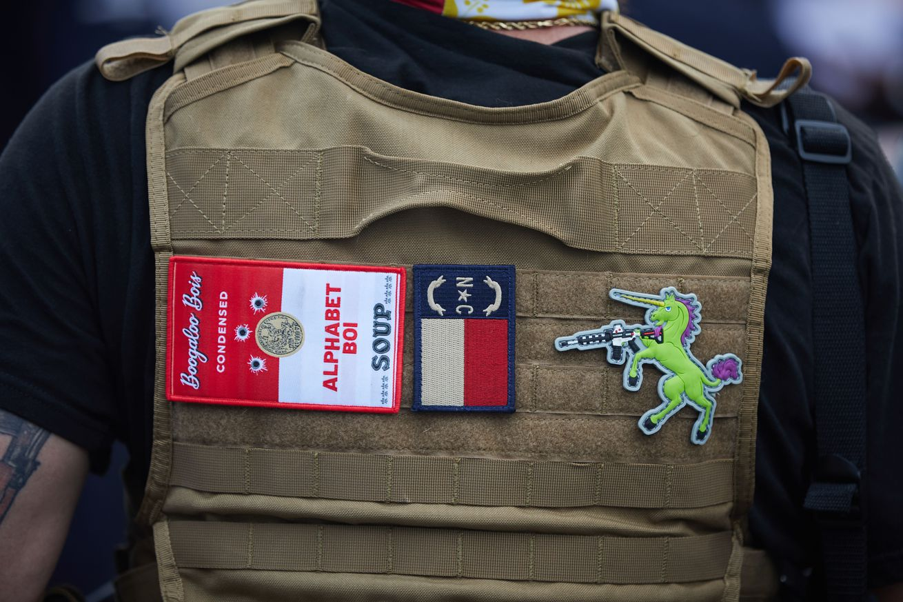 A member of the far-right militia, Boogaloo Bois, walks next to protestors demonstrating outside Charlotte Mecklenburg Police Department Metro Division 2 just outside of downtown Charlotte, North Carolina, on May 29, 2020