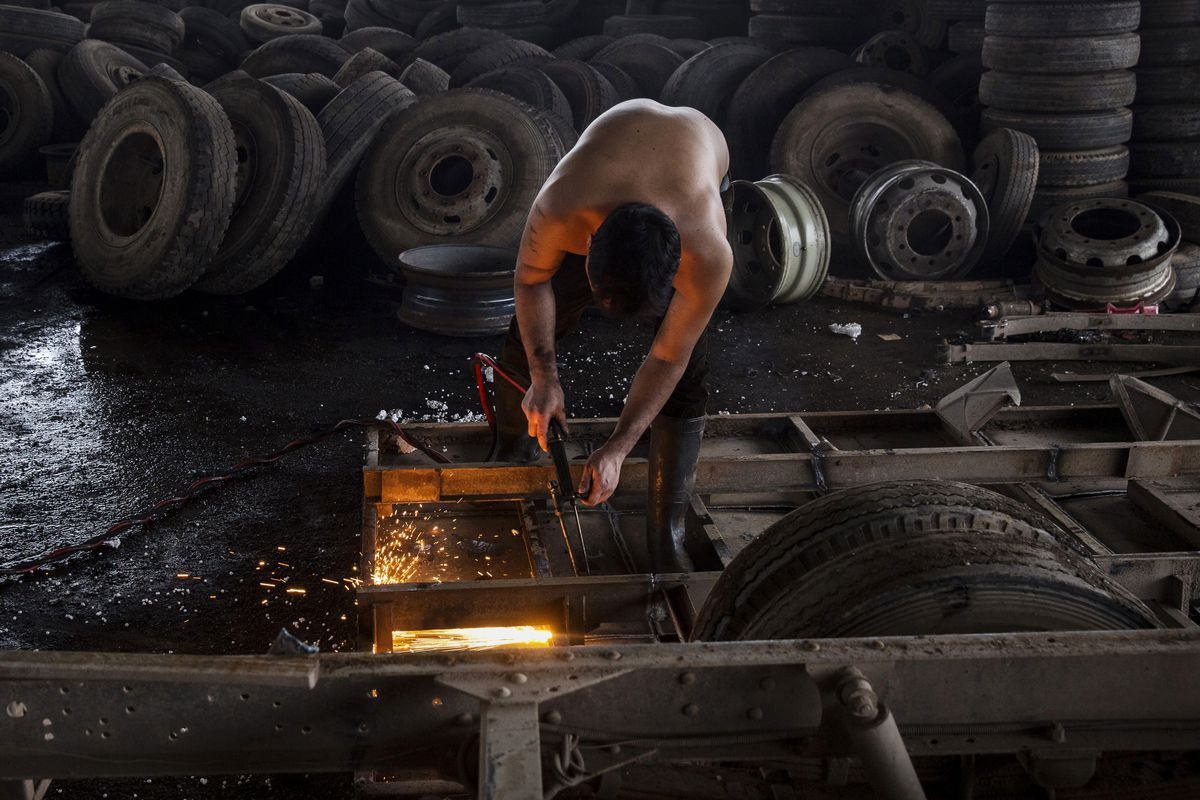 A Chinese labourer dismantles a truck that was taken off the road by authorities on September 25, 2015 in Zhejiang, China. The scrapyard is part of a government program to remove tens of thousands of polluting vehicles from the road.