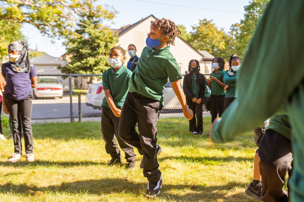 Students wearing green shirts dance together on the first day of school at Paul Robeson Malcom X Academy.