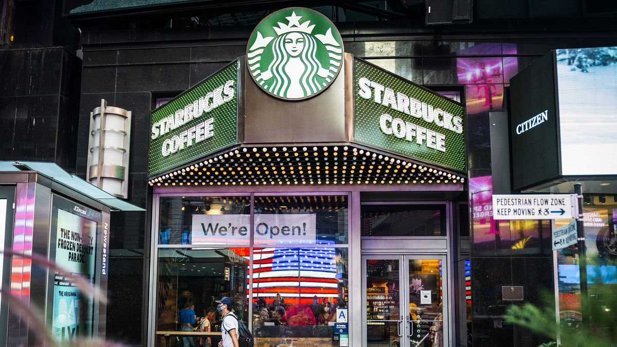 """The exterior of a Starbucks Coffee store with an American flag and a """"we're open"""" sign in the window."""