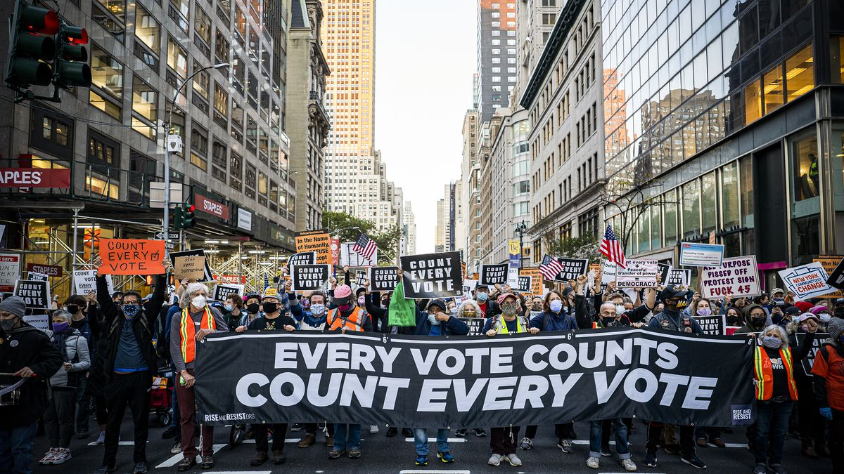 """Protesters fill a city street carrying a sign reading, """"Every vote counts. Count every vote."""""""