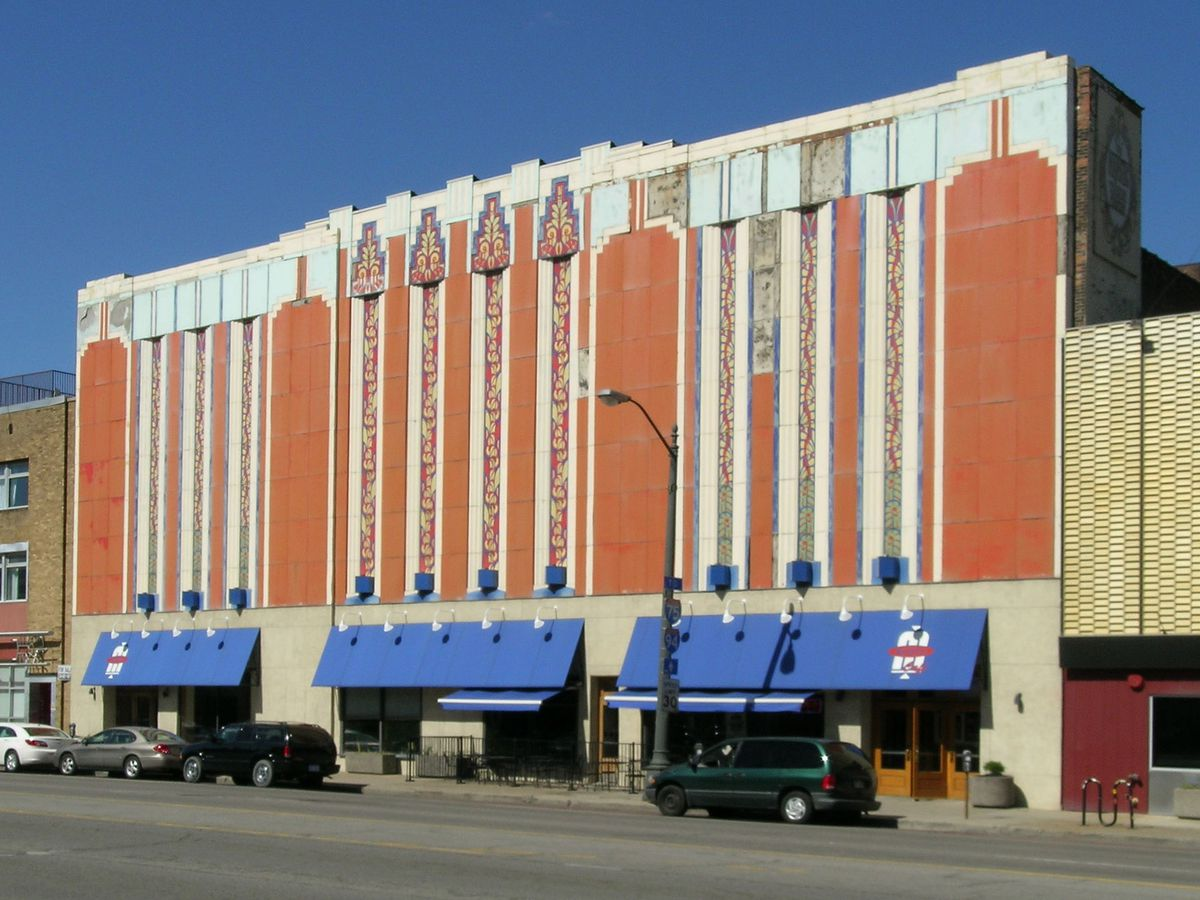 A tall, rectangular with brown paint and some Aztec-inspired Art Deco details on top. There's blue awnings above the ground-floor windows, one of which has a big M for Majestic.