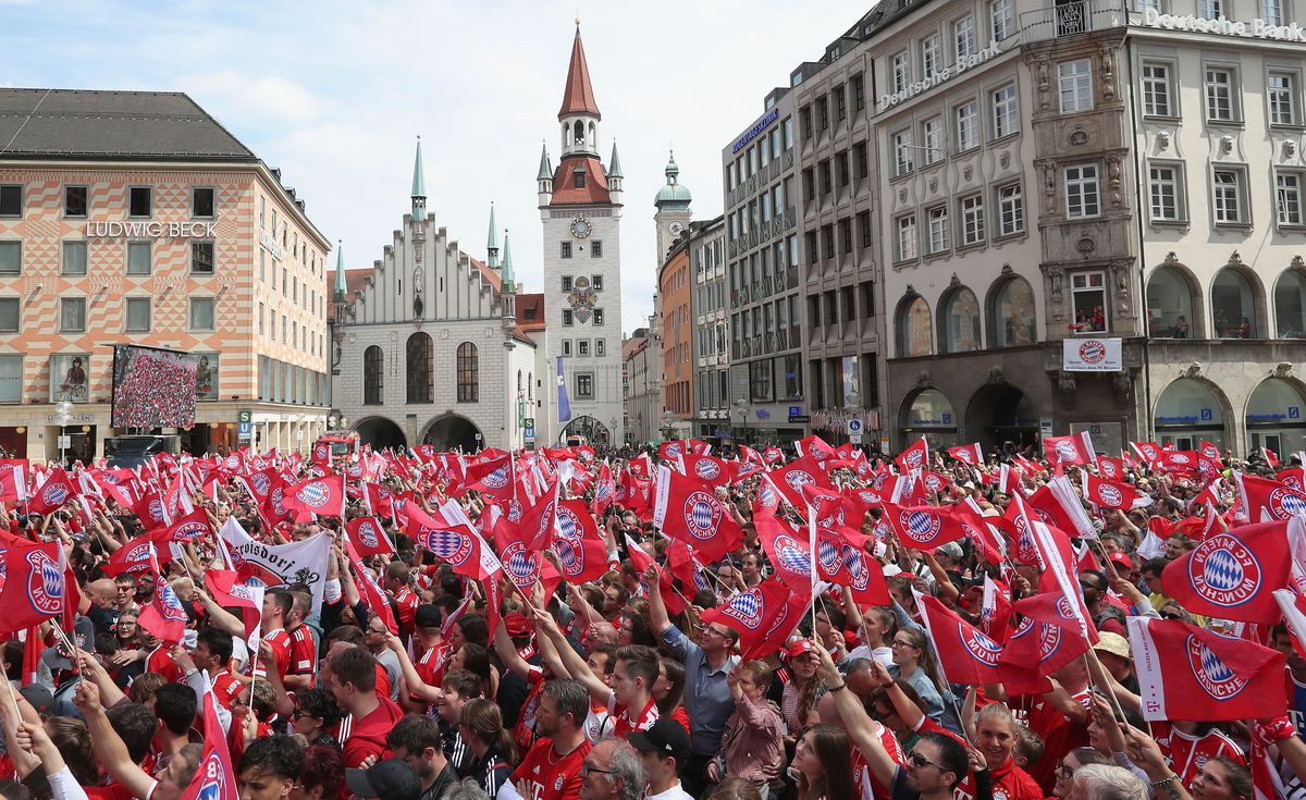 MUNICH, GERMANY - MAY 20: Fans of FC Bayern Muenchen wave with flags wating for the team to celebrate the German Championship title for the season 2017/18 on the balcony of the town hall on May 20, 2018 in Munich, Germany.