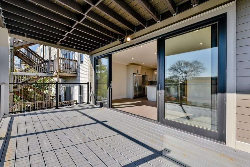 A sizable empty deck with a cover and sliding doors leading to it.