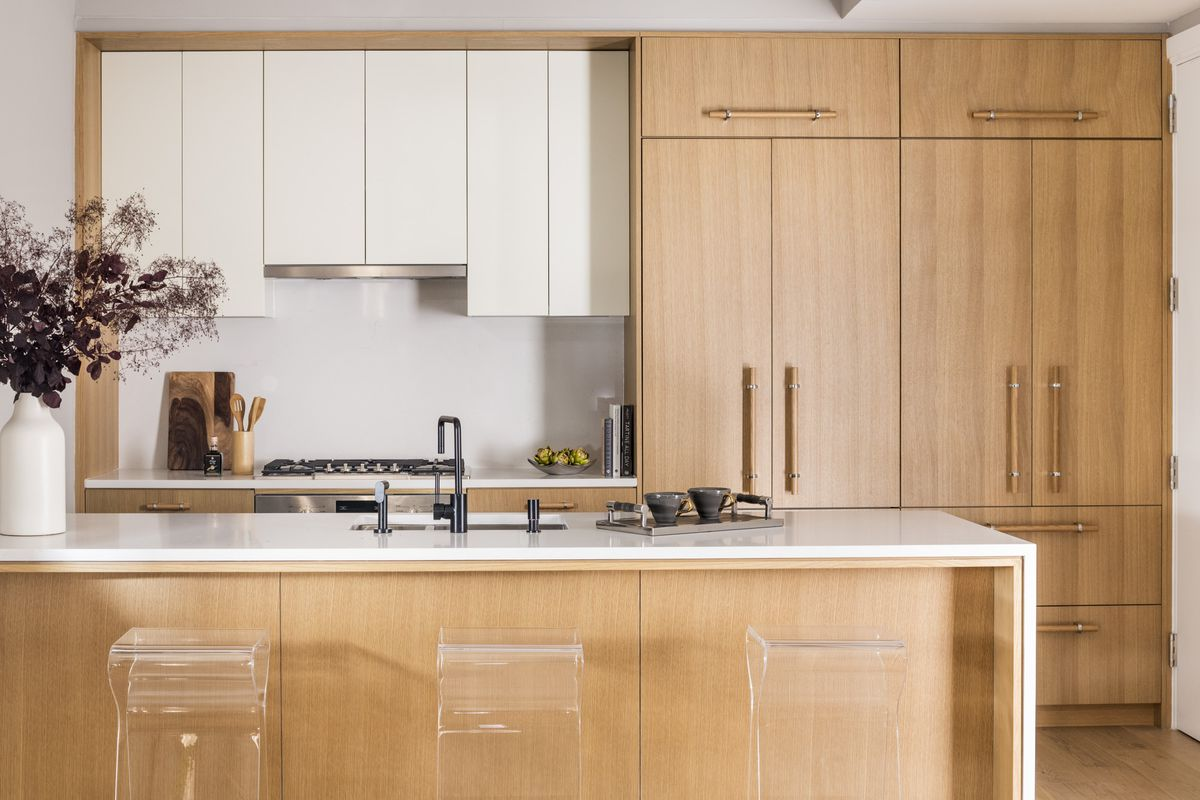 A kitchen with white and wooden cabinetry and an island with three clear high top chairs.