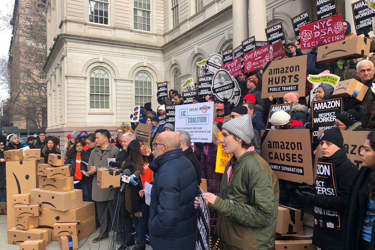 Protestors rally against Amazon outside New York City's City Hall before a hearing about the company's HQ2 plans.