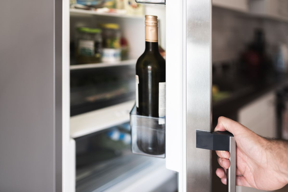 Sleek refrigerator door being opened by a white male hang, with a bottle of wine visible on the door shelf